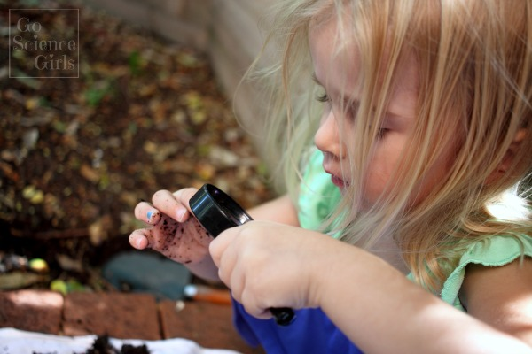 Using magnifying glass to examine dirt