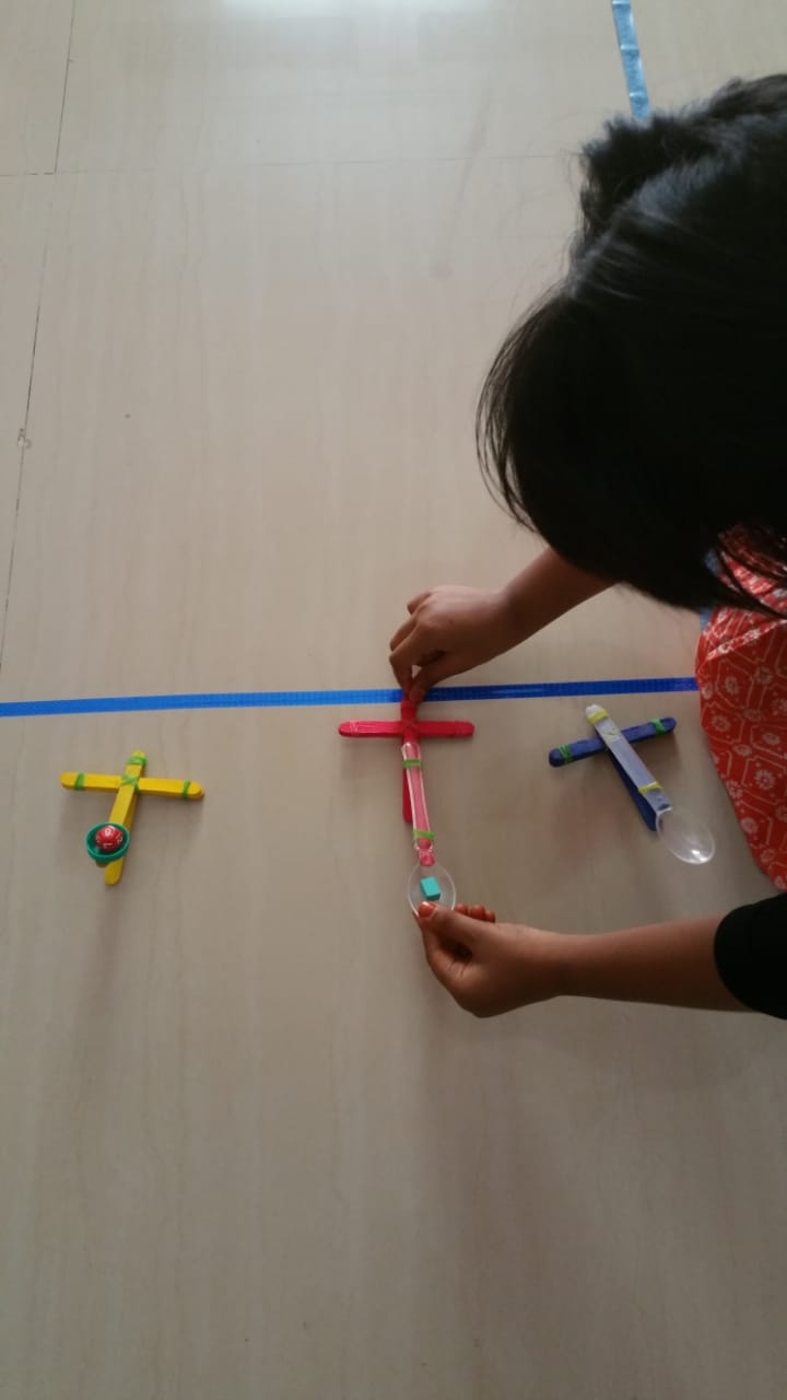Using magnatiles to measure DIY catapult projectile heights - fun STEM activity for kids combining science, engineering and maths with play