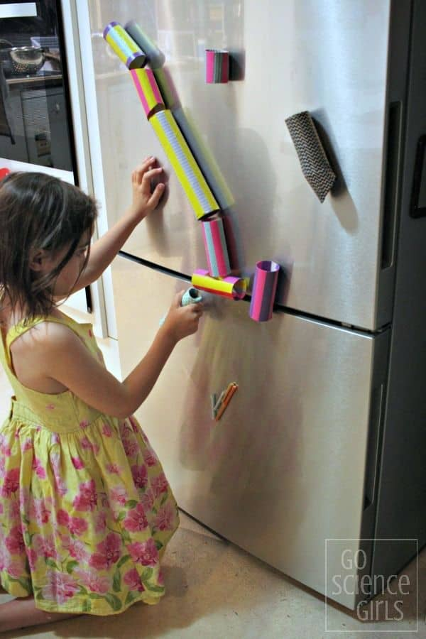 7 year old decorating magnetic marble run on the fridge